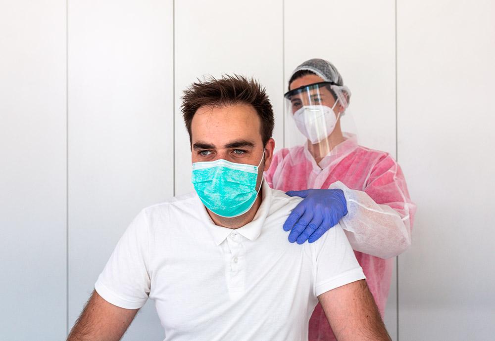 Una fisioterapeuta equipada con un EPI atiende a un paciente de Coronavirus
