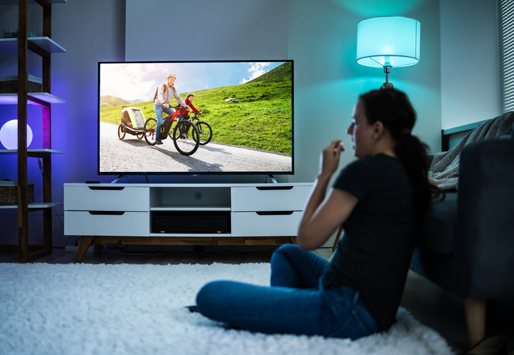 Una mujer ve un anuncio durante el confinamiento en el salón de su casa