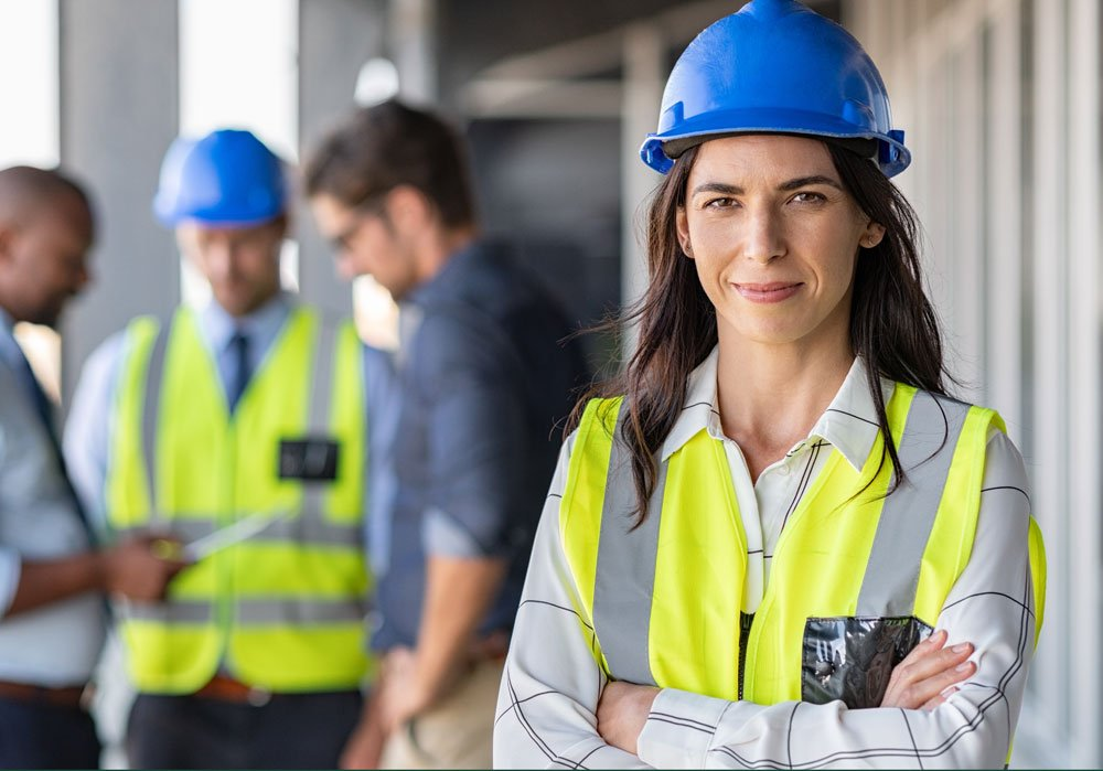 Mujer ingeniera con casco azul de brazos cruzados mirando a la cámara
