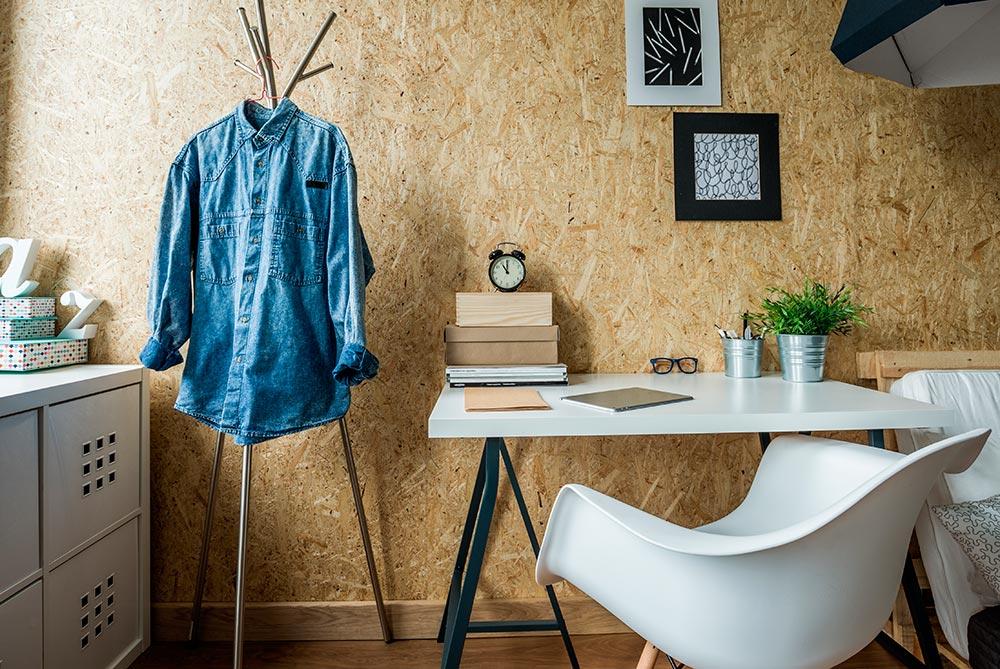 habitación de estudiantes con mesa de estudio y camisa vaquera en un perchero