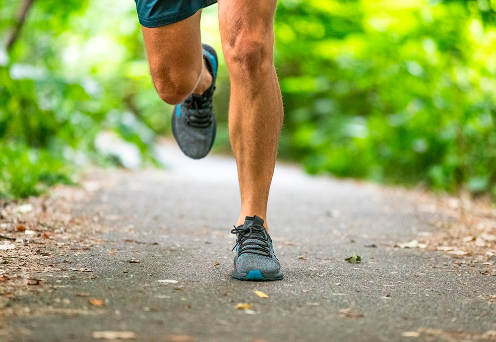 Piernas de un runner practicando running en un parque.
