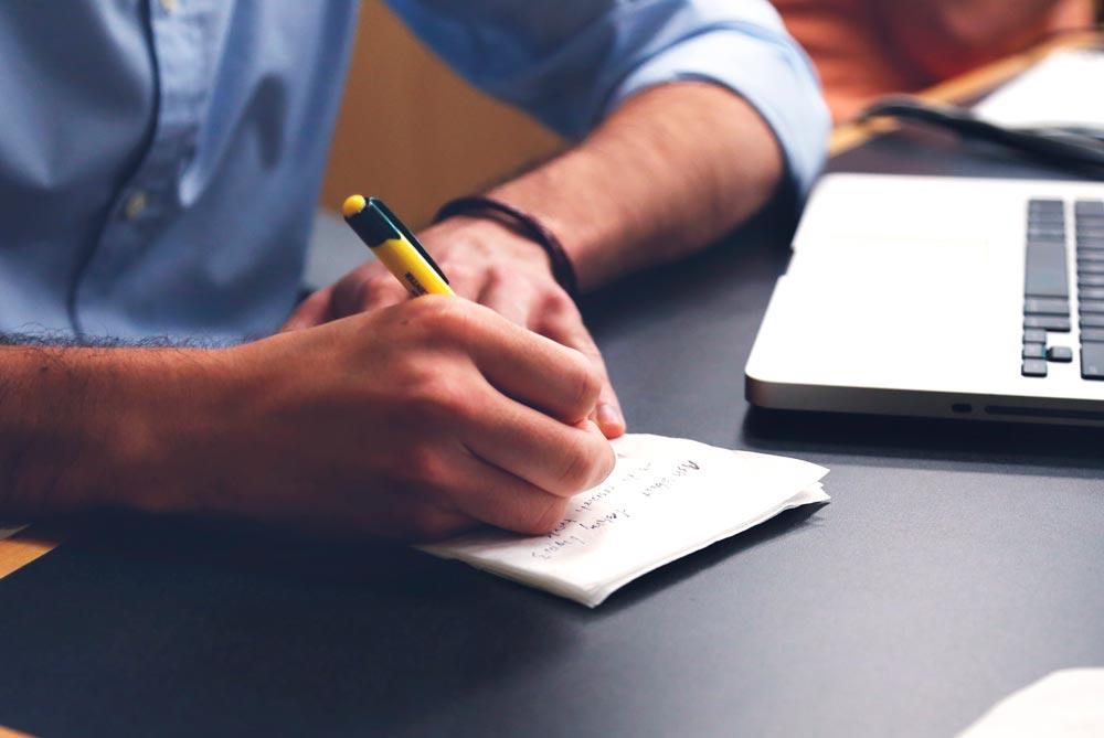 Mano escribiendo en unos papeles y portátil de fondo