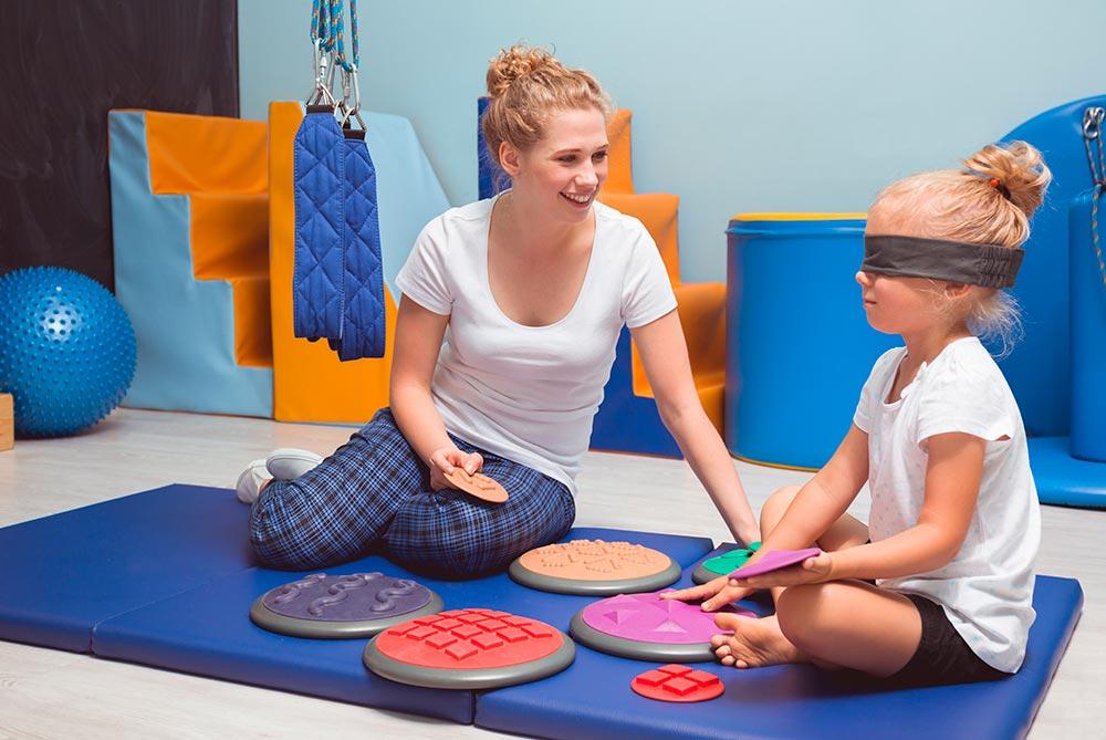 Terapeuta sentada sobre una cochoneta con una niña con los ojos cerrados y algunos juguetes terapeúticos
