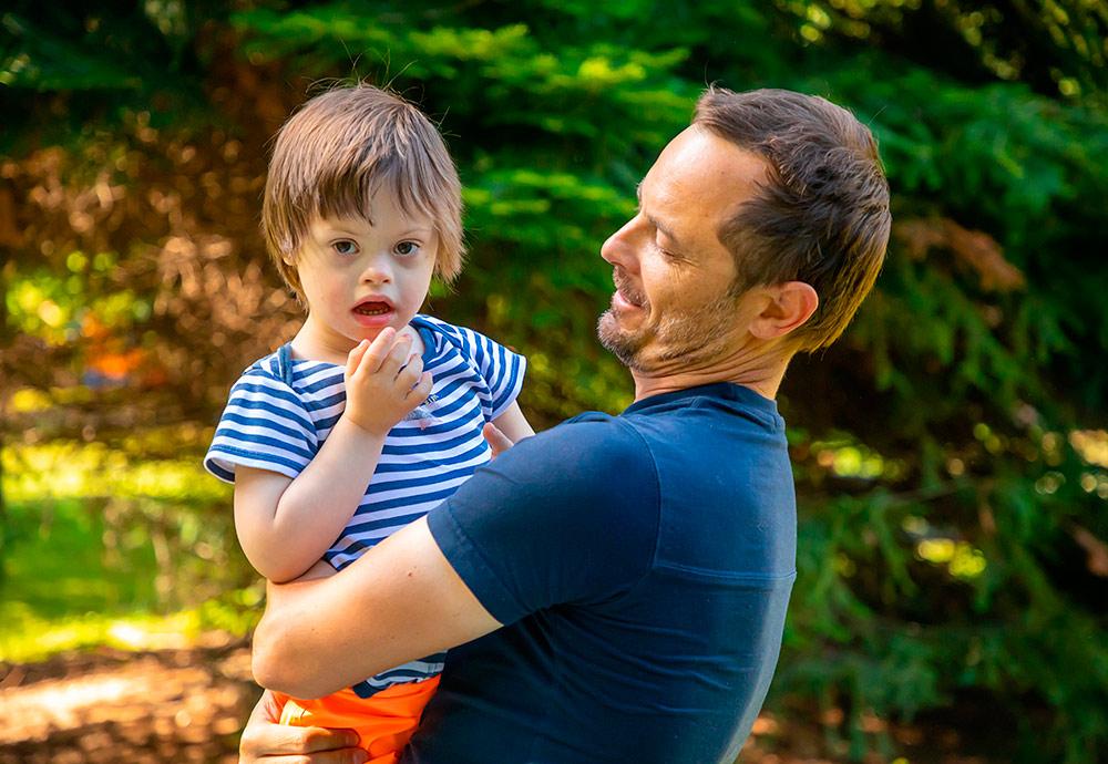 Un padre sostiene en brazos a un niño con síndrome de Down.